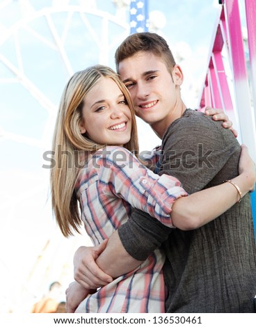 Close up of an attractive young couple hugging with their heads together while visiting a funfair amusement park with rides, being romantic and smiling. - stock photo