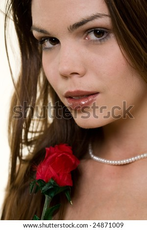 Close up of an attractive young long hair brunette woman wearing a formal red satin gown holding a red rose - stock photo