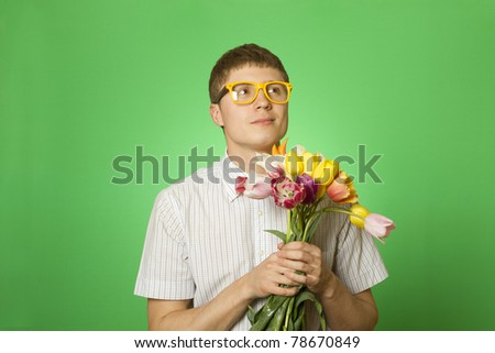 Close-up of an attractive young man in kubashke bow tie and glasses holding a bouquet of tulips. Nerd - stock photo