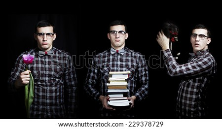 Close-up of an attractive young man in shirt bow tie and glasses holding a tulip a  black rabbit bunny with a red bow ,and a stack of books isolated on black - stock photo