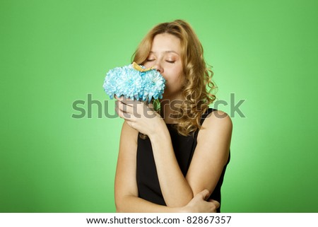 Close-up of an attractive young woman holding a gift bouquet of blue chrysanthemums sits on colors yellow butterfly