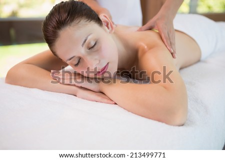 Close up of an attractive young woman receiving back massage at spa center - stock photo