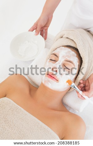 Close-up of an attractive young woman receiving treatment at spa center - stock photo