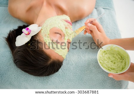 Close-up of an attractive young woman receiving treatment at spa center