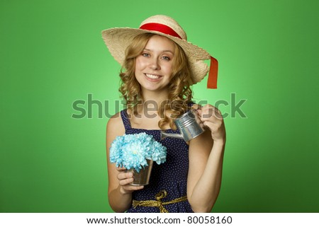 Close-up of an attractive young woman watering bouquet of chrysanthemums in a steel bucket of metal watering can
