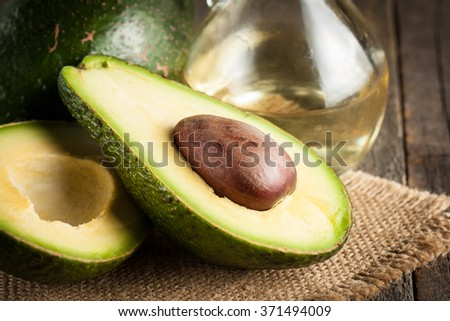 Close-up of an avocado and avocado oil on wooden table. Healthy food concept.