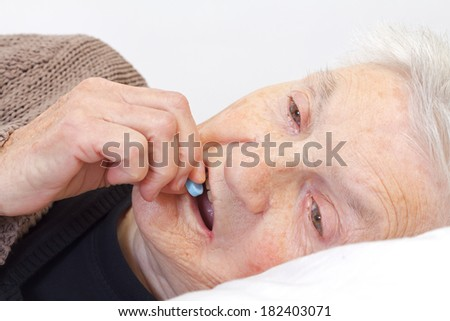 Close up of an elderly eating holding in her bed - stock photo