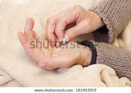 Close up of an elderly hand holding pills - stock photo