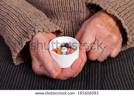 Close up of an elderly woman's hand holding pills. - stock photo