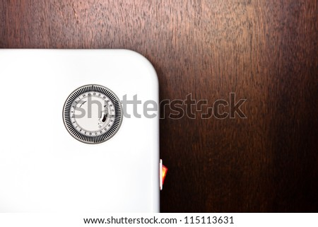 Close up of an electric heater with a timer switch against a wooden background - stock photo