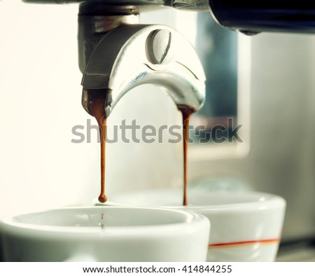 Close up of an espresso machine making a cup of coffee. - stock photo