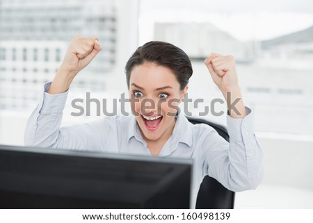 Close-up of an excited businesswoman clenching fists as she looks at the computer screen in a bright office