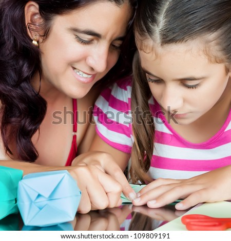 Close-up of an hispanic mother and daughter making origami at home - stock photo