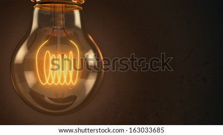 Close up of an illuminated vintage hanging light bulb over dark background - stock photo
