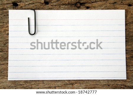 close up of an index card with a black paper clip on an old piece of wood. - stock photo