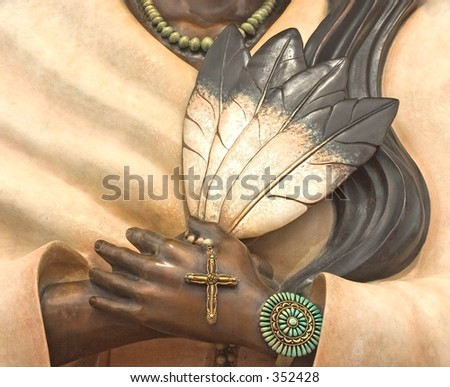 Close-up of an Indian woman's hands holding four feathers and a crucifix at a church in Santa Fe, NM.