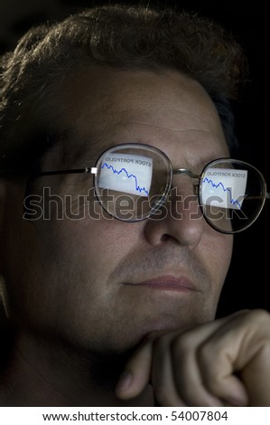 close-up of an investor with an ascending stock portfolio graph reflected in his glasses. - stock photo
