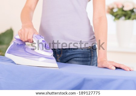 Close-up of an iron. Stereotypical housewife ironing on ironing board - stock photo