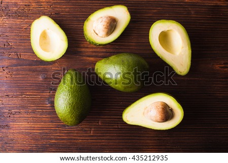 Close-up of an juicy organic avocado on wooden table - stock photo