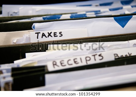 Close-up of an office shelves full of different files, focus on Taxes - stock photo