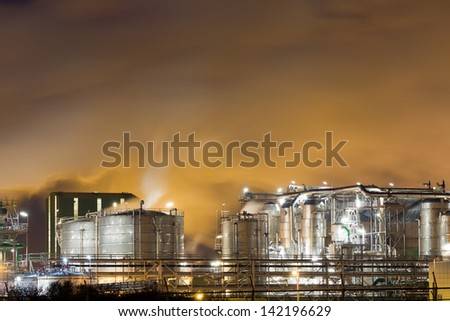 Close-up of an oil-refinery plant and a yellow night-sky - stock photo