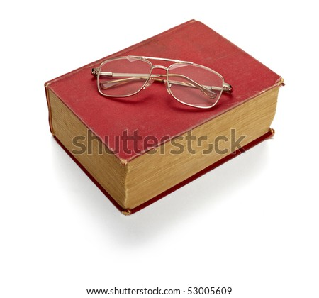close up of an old book and eyeglasses on white background with clipping path - stock photo
