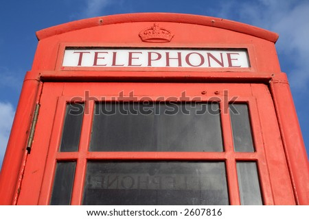 Close up of an old English red telephone box with a blue sky. - stock photo