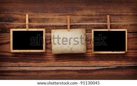 close up of an old photo and clothes peg on a wooden background - stock photo