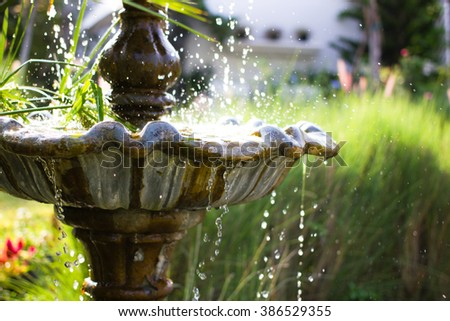 Close-up of an old stone fountain with dripping water in vintage garden - stock photo