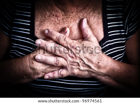 Close up of an old woman's hands over her chest - stock photo