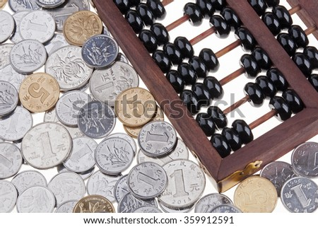 Close up of an old wooden Chinese Abacus and Chinese coins - stock photo