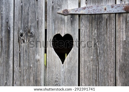 close-up of an old wooden door with a carved heart - stock photo