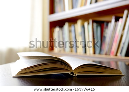 Close-up of an open book , on a wooden table, with bookshelvClose-up of an open book , on a wooden table, with bookshelves in the background, as an invitation to study literaturees in the background,  - stock photo