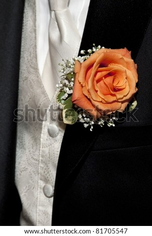 Close up of an orange rose boutonniere on a groom's tux with ivory vest and tie showing.