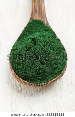 Close-up of an organic spirulina algae in wooden spoon - stock photo
