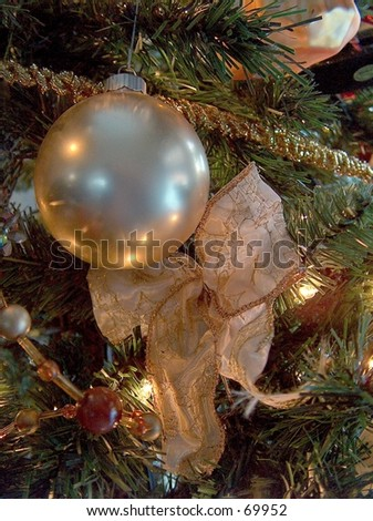 Close up of an ornament and bow in a Christmas Tree. - stock photo