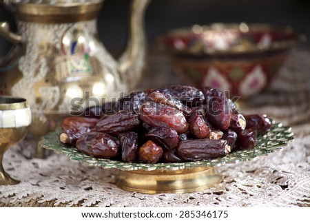 Close-up of an ornamental bowl of dried dates with kettle and glass on tablecloth - stock photo