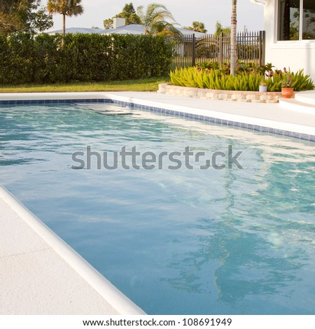 Close up of an outdoor swimming pool and indigenous landscaped plants in the backyard of a home in Florida. - stock photo