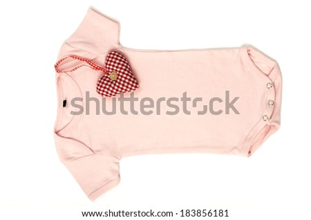 Close up of an pink baby onesie with a smal red heart on it isolated