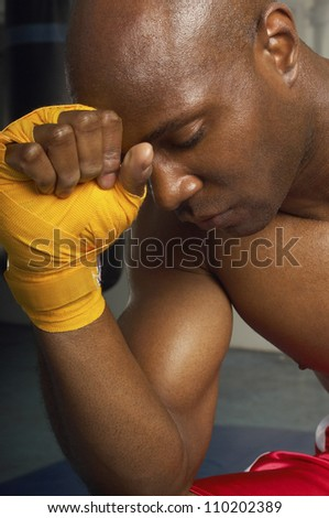 Close-up of an upset African American male boxer with head on wrapped hand - stock photo