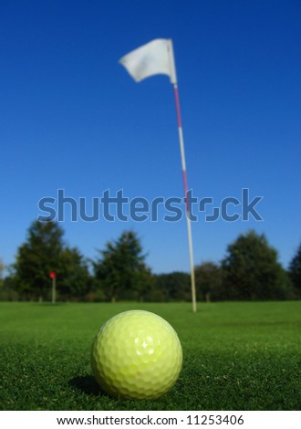 Close up of an yellow golf ball on the green next to the flag of hole