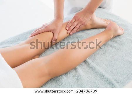 Close-up of an young woman receiving leg massage at spa center
