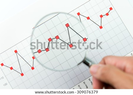 Close up of analysing report graph with magnifying glass - stock photo