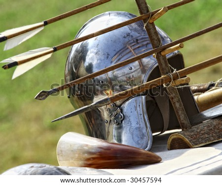 close up of ancient metal helmet and arrows  background - stock photo
