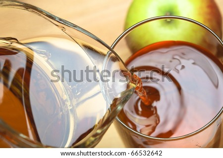 Close up of apple juice being poured from a glassware jug into a glass over wooden table.  Apple in top right frame.