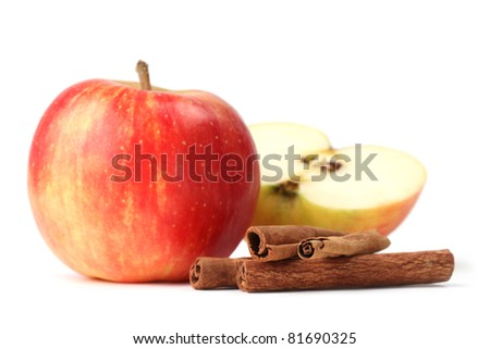 Close-up of apples and cinnamon sticks on white background. Shallow dof