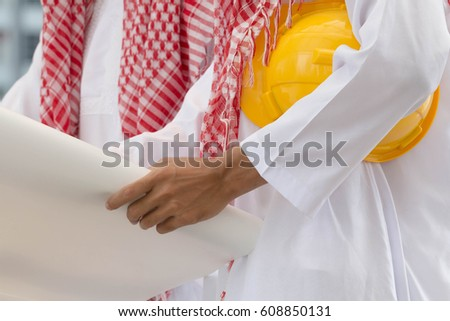 Close up of Arab businessman holding paper plan and yellow safety helmet.