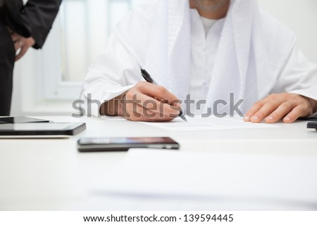 Close up of Arab businessman signing the contract. Focus is on hand - stock photo