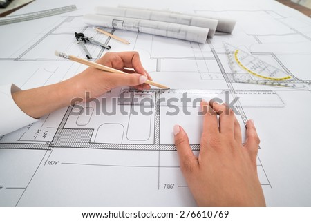 Close-up Of Architect Hands Working On A Blueprint In Office. Blueprints were created by photographer - stock photo