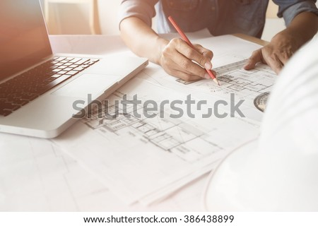 Close up of Architect sketching a construction project with laptop at work place. - stock photo